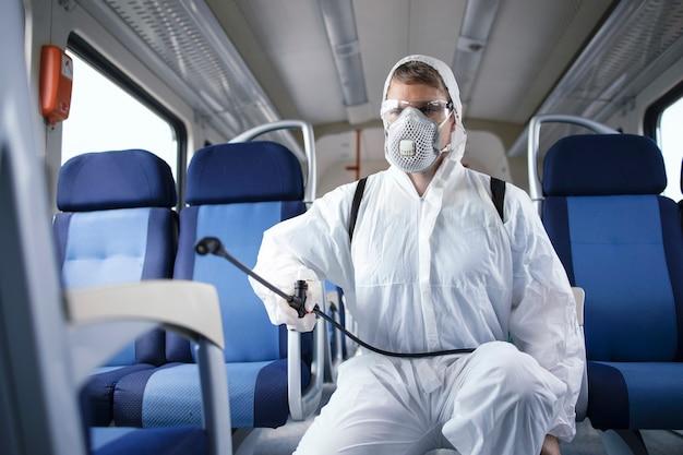 白い防護服を着た男が、伝染性の高いコロナウイルスの拡散を防ぐために、地下鉄の電車内を消毒および消毒します。
