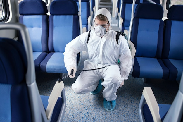 Мужчина в белом защитном костюме дезинфицирует и дезинфицирует салон метро, чтобы остановить распространение очень заразного вируса короны