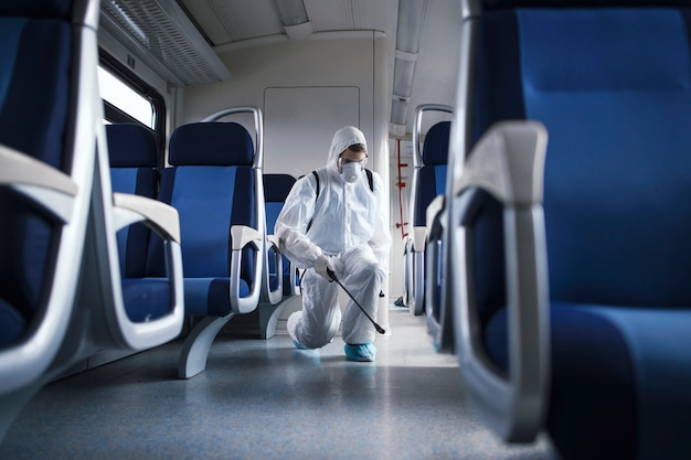 흰색 보호 복을 입은 남자가 전염성이 높은 코로나 바이러스의 확산을 막기 위해 지하철 열차 내부를 소독하고 살균합니다.