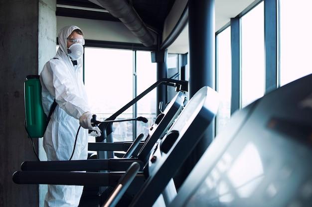 흰색 보호 복을 입은 남성이 전염성이 높은 코로나 바이러스의 확산을 막기 위해 러닝 머신 달리기 트랙을 소독하고 살포합니다.