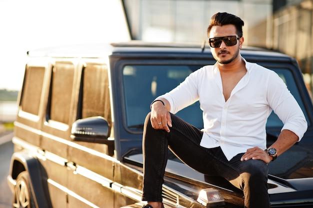 白いシャツとサングラスの男が黒いsuv車の近くでポーズ