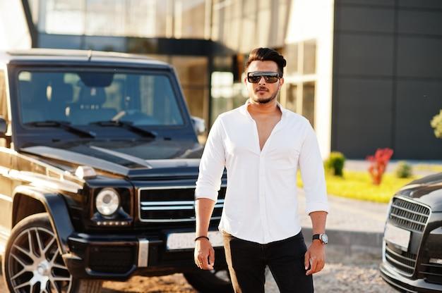 白いシャツとサングラスの男が黒いsuv車の近くでポーズ Premium写真