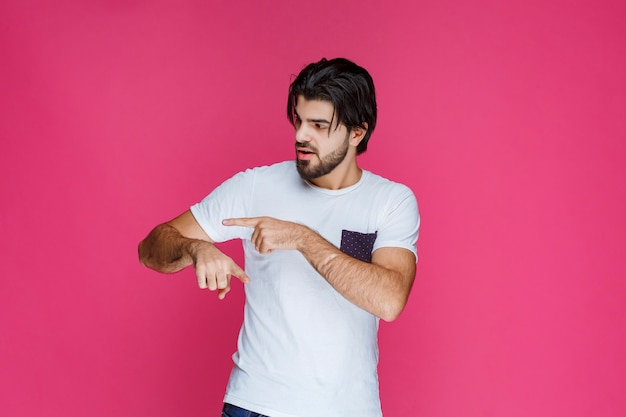 Человек в белой рубашке проверяет время на своих часах.