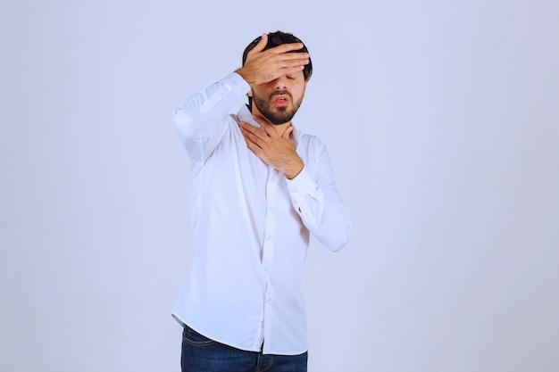 흰 셔츠를 입은 남자가 얼굴을 가리고 슬프고 두통이 있습니다.
