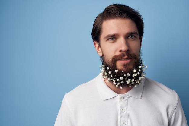 花の装飾の青い背景を持つ白いシャツの感情のひげの男