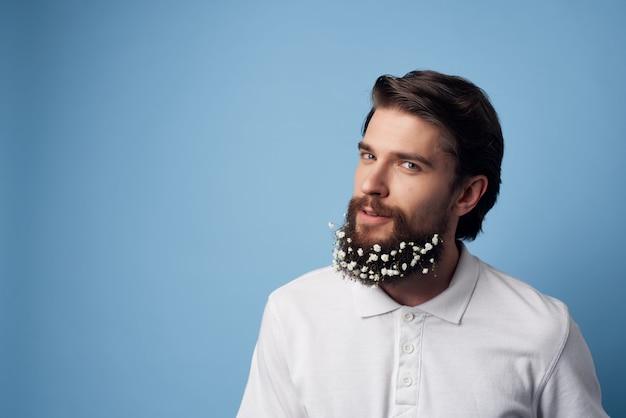 ひげのヘアケアファッション青い背景の白いシャツの花の男