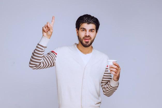 커피 컵을 들고 그것을 즐기는 흰 셔츠에 남자.