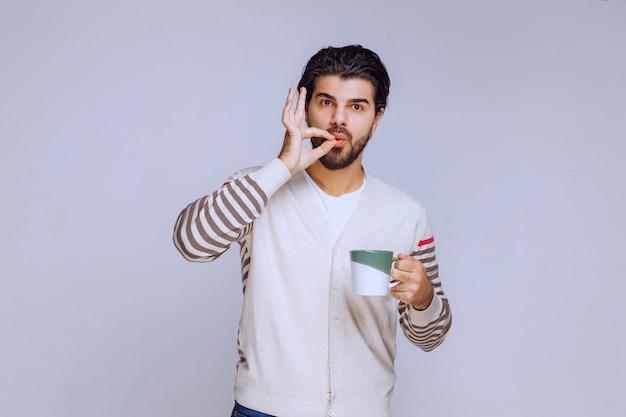 コーヒーカップを持って楽しんでいる白いシャツの男。
