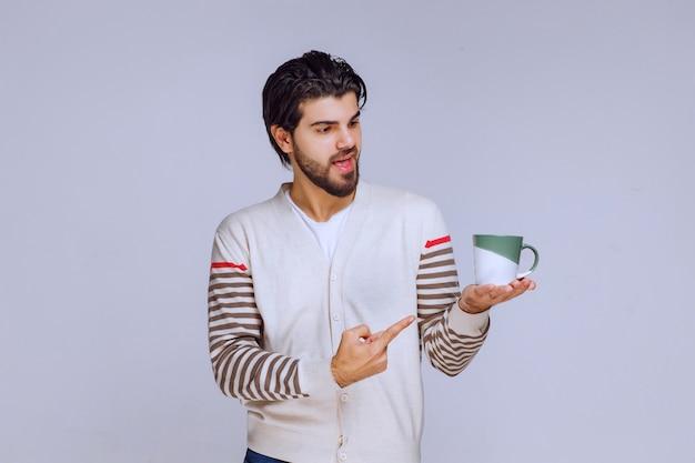 Человек в белой рубашке держит чашку кофе и указывая на нее.