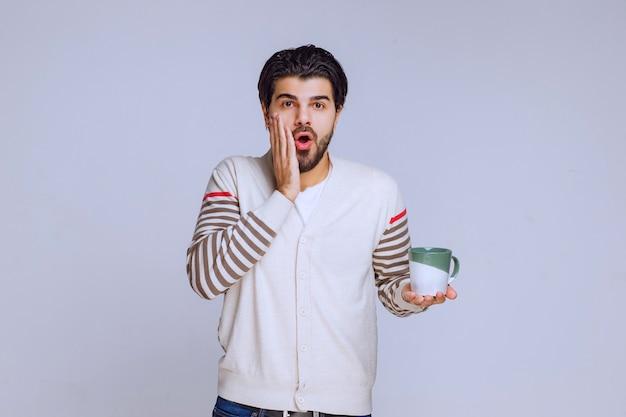 コーヒーのマグカップを持っている白いシャツを着た男は驚いたように見えます。