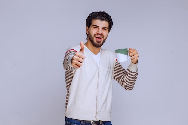 コーヒーのマグカップを保持し、良い手サインを作る白いシャツの男。