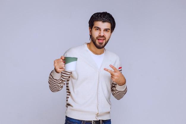 コーヒーのマグカップを持ってそれを見せている白いシャツの男。