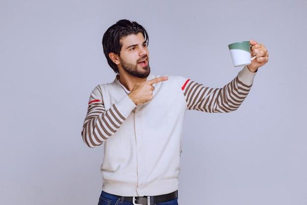 커피 잔을 들고 그것을 보여주는 흰 셔츠에 남자.