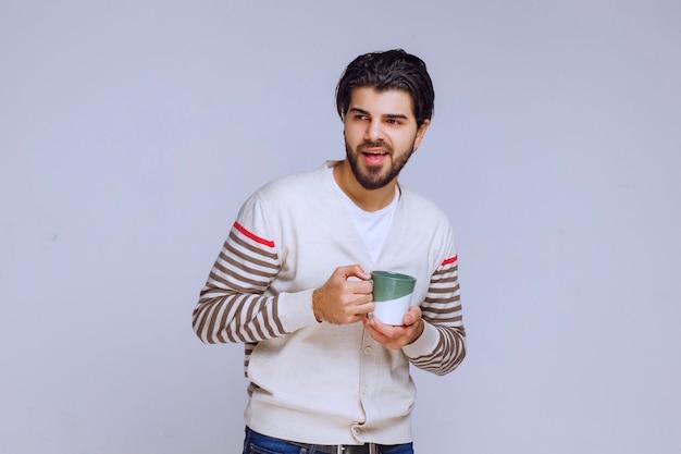 コーヒーのマグカップを持って、コーヒーを飲み、元気を感じている白いシャツを着た男。