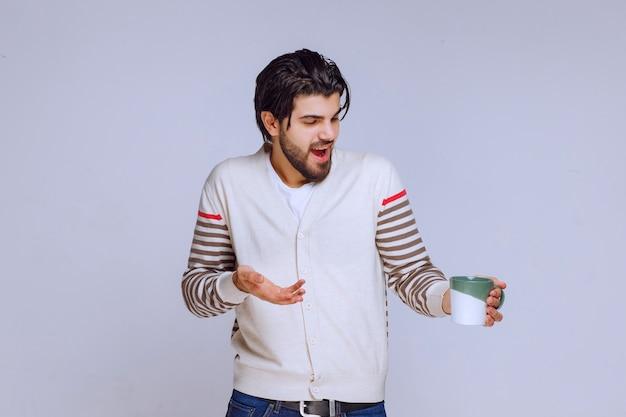 コーヒーマグカップを持ってポーズをとっている白いシャツの男。