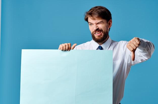 Человек в белой рубашке, держа знамя в руках эмоции маркетинга голубой фон. фото высокого качества