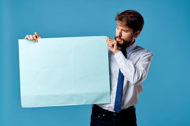 青い背景のマーケティングの感情の手でバナーを保持している白いシャツの男
