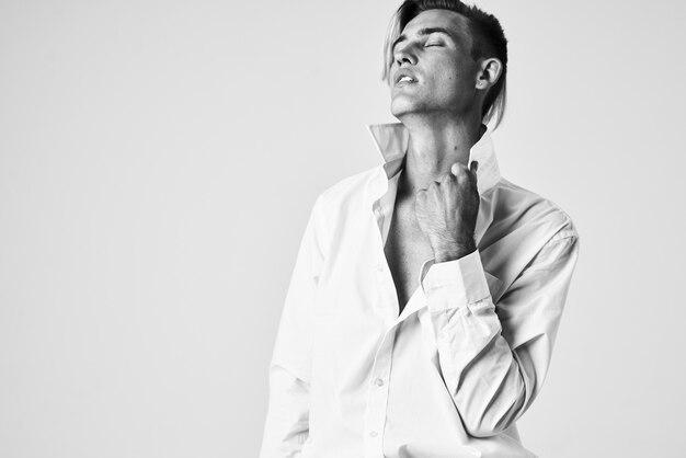 Мужчина в белой рубашке держит воротник в элегантном стиле позирования