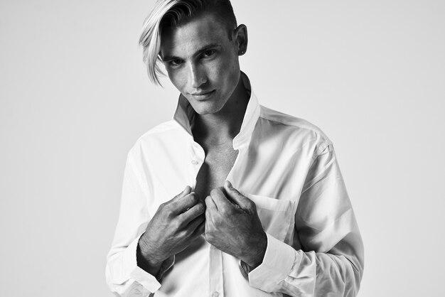 Человек в белой рубашке, держащий воротник, элегантный стиль, уверенность в себе.