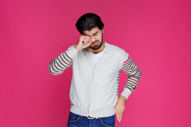 Мужчина в белой рубашке выглядит усталым и сонным.