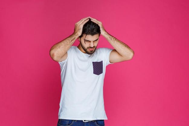 白いシャツを着た男は悲しくてがっかりしているように見えます。