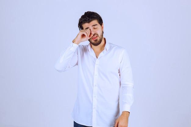 Мужчина в белой рубашке выглядит сонным или грустным.