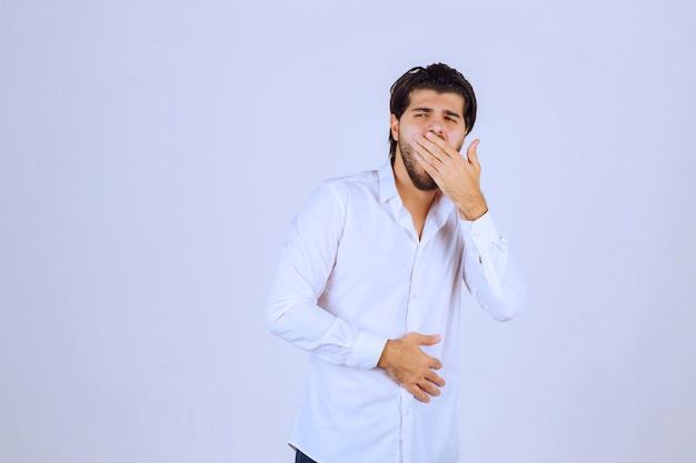 흰 셔츠를 입은 남자는 졸리거나 슬퍼 보입니다.