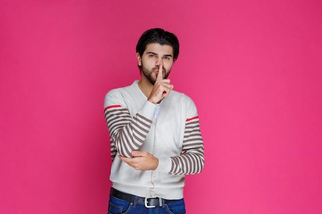Человек в белой рубашке делает знак замолчать и перестать говорить.