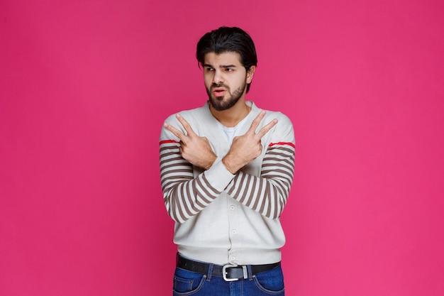 평화 손 기호를 만들고 메시지를 보내는 흰 셔츠에 남자.