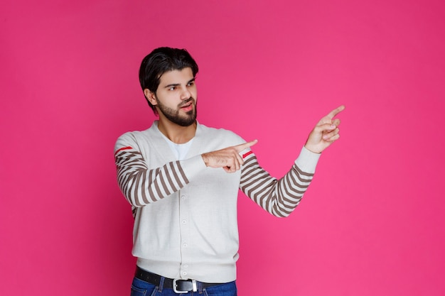 Мужчина в белой рубашке указывает и показывает что-то в правой части.