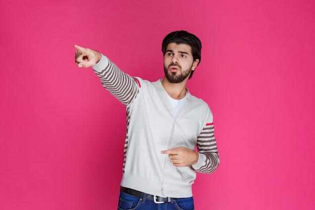 Мужчина в белой рубашке указывает и показывает что-то на левой стороне.