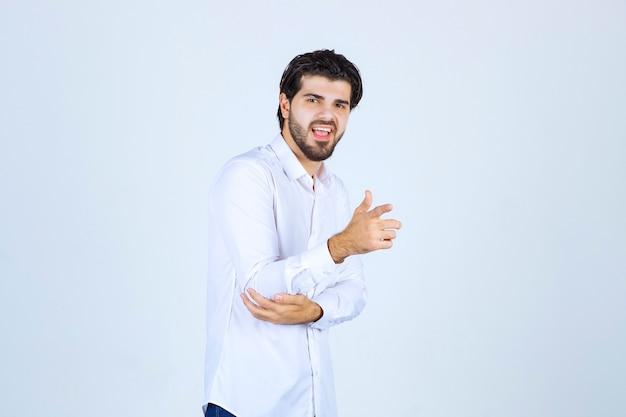 그의 동료를 가리키는 흰 셔츠에 남자.