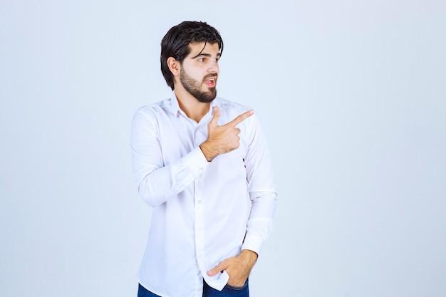 오른쪽에 뭔가 가리키는 흰 셔츠에 남자.