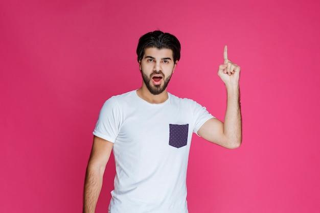上の何かを指している白いシャツの男。