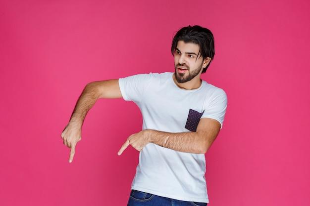 人差し指で何かを指している白いシャツを着た男。