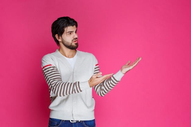 どこかを指して誰かを紹介したり、方向を示したりする白いシャツを着た男。