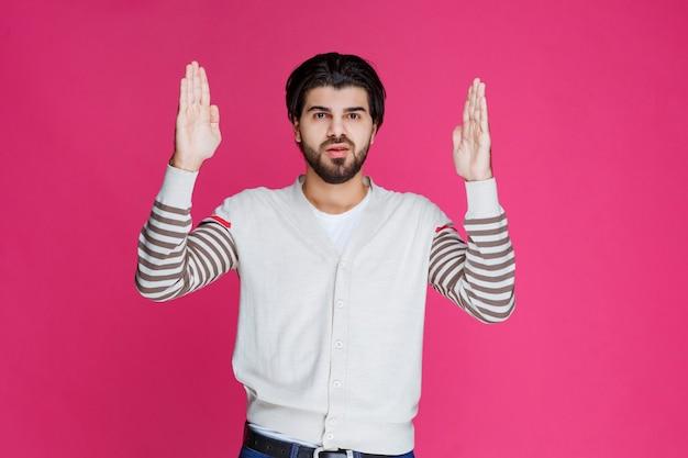 Мужчина в белой рубашке указывает куда-то и представляет кого-то или просто показывает направление.