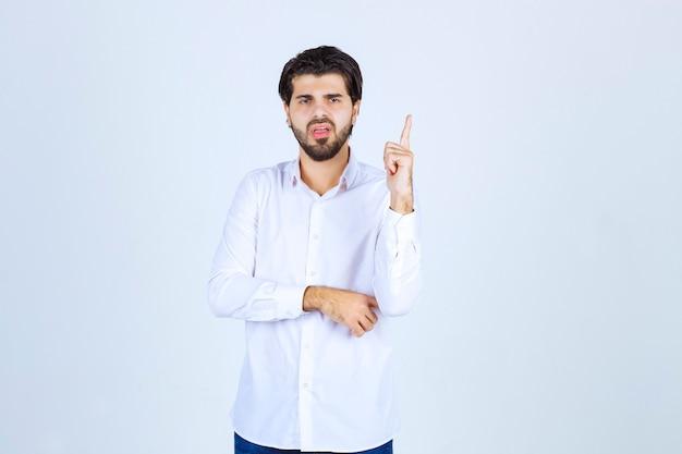 Человек в белой рубашке, указывая вверх.