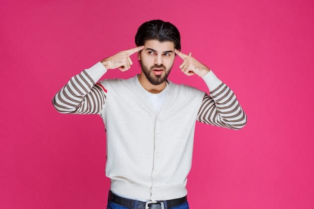 Человек в белой рубашке, прикладывая руку к голове, как будто он глубоко думает и пытается вспомнить