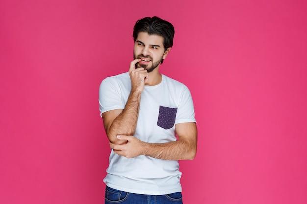 Человек в белой рубашке прикладывает руку к лицу и думает.