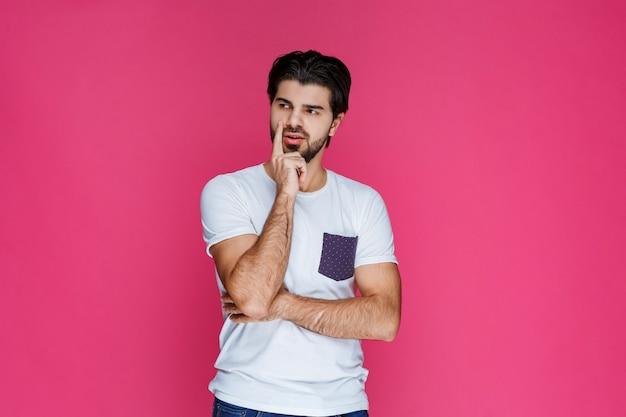 그의 얼굴에 손을 넣고 생각하는 흰 셔츠에 남자.