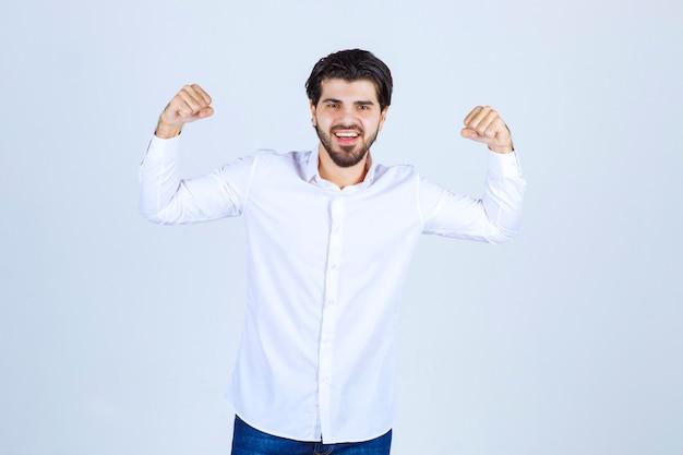 彼の腕の筋肉と拳を示す白いシャツを着た男。