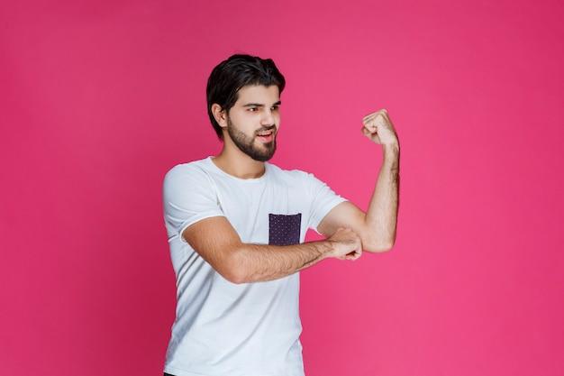 彼の拳と上腕二頭筋を示す白いシャツの男。