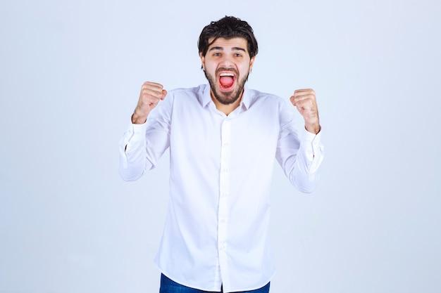 彼の拳を示し、成功を感じている白いシャツの男