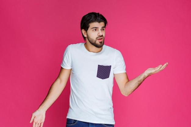 흰색 셔츠를 입은 남자는 그가 주제에 대해 전혀 모른다는 것을 보여줍니다.