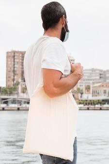 Мужчина в белой рубашке с помощью перерабатываемой хозяйственной сумки