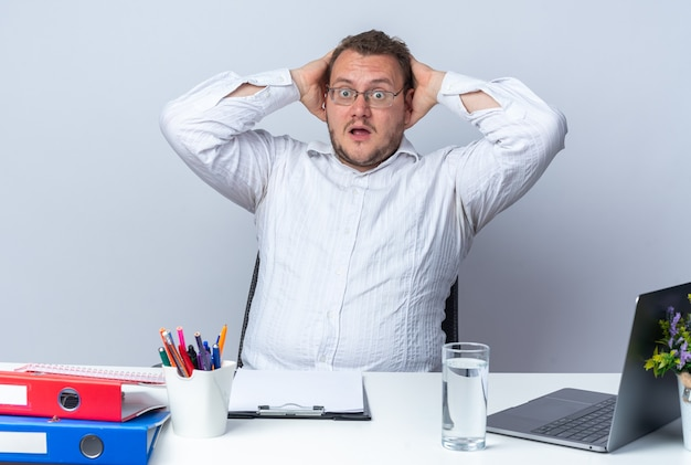 眼鏡をかけている白いシャツの男は、白のラップトップオフィスフォルダーとクリップボードを持ってテーブルに座って驚いて驚いた