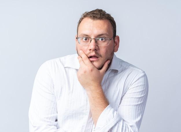 안경을 쓴 흰 셔츠를 입은 남자가 흰 벽 위에 서서 놀라고 놀랐다