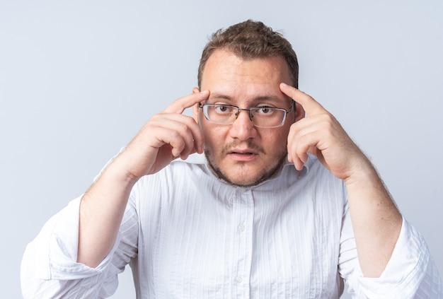 안경을 쓴 흰 셔츠를 입은 남자는 손가락이 흰 벽 위에 서 있는 그의 관자놀이를 혼란스럽고 매우 불안하게 가리키고 있다