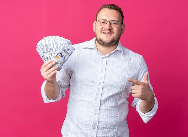 안경을 쓴 흰 셔츠를 입은 남자 집게 손가락으로 돈을 가리키는 현금을 들고 분홍색 벽 위에 유쾌하게 서서 웃고 있는 남자